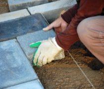sidewalk pavement construction works laying bricks on sand